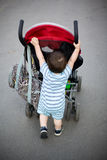Baby pushing stroller Stock Images