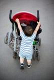 Baby pushing stroller Stock Images