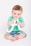 Baby Puts Letter A in His Mouth. 8 month year old baby sits on a white background holding a white letter A to his mouth looking to the left. dressed in a cute Stock Photo