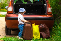 Baby puts the suitcase in the car Stock Images