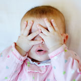 Baby putting hands on face stock photos