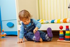Baby putting on sandal Stock Photography