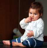 Baby putting something in mouth Royalty Free Stock Photo