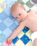 Baby on Quilt. Cute baby lying on back on a multicolored quilt with arm extended Stock Photo