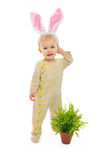 Baby with rabbit ears standing near pot with plant Royalty Free Stock Image