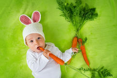 Baby in rabbit hat eating carrot Royalty Free Stock Photos