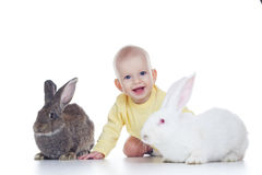 Baby and rabbits. Little baby girl playing with two rabbits Stock Images