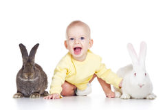 Baby and rabbits. Little baby girl playing with two rabbits Stock Photography