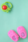 Baby rattle and booties on green background Royalty Free Stock Images