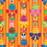 Baby rattle cartoon head decor wall seamless pattern. This illustration is drawing vertical baby rattle with animal head decor on stripe wallpaper in orange Royalty Free Stock Image