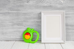 Baby rattle and photo frame on wooden background Royalty Free Stock Image