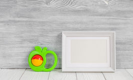 Baby rattle and photo frame on wooden background Royalty Free Stock Images