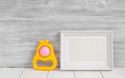 Baby rattle and photo frame on wooden background Royalty Free Stock Photo