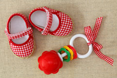 Baby rattle and red shoes Royalty Free Stock Photos
