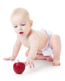 Baby reaches for an apple. Baby reaches for an red apple sitting on the floor Stock Images