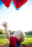 Baby Reaching for Balloons Stock Image