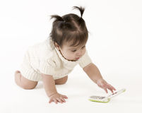 Baby reaching for cell phone. Adorable baby girl crawling and reaching for a cell phone stock image