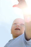 Baby Reaching for the Sky. A baby boy reaching his hand toward the sky with the sun glowing behind him Royalty Free Stock Photos