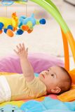Baby reaching for toy. Baby reaching for colorful toy on playmat stock photography