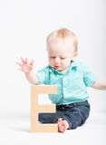 Baby Reaching for Wooden Letter E. A 6 moth old baby reaches out to grab a wooden letter e Stock Photo