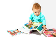 Baby read the magazine. On white Royalty Free Stock Photography