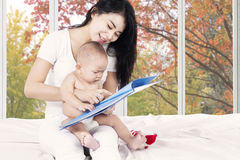 Baby read story book with mother Royalty Free Stock Photos