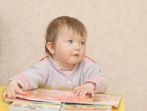 Baby, reading the book. Baby girl, reading the book Stock Image