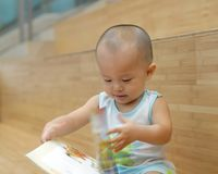 Baby reading book. A Chinese baby is reading a book. His hand is touching the page Stock Images