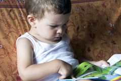 Baby reading the book. A little child is reading a book sitting in a sofa Stock Photo