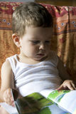 Baby reading the book. A little child is reading a book sitting in a sofa Royalty Free Stock Photos