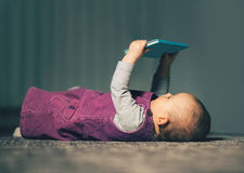 Baby reading a book on back Royalty Free Stock Image