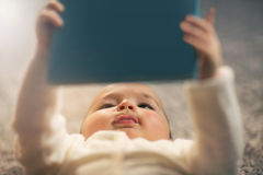 Baby reading a book on back Royalty Free Stock Images