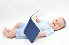 Baby reading a book on back. On white bed Royalty Free Stock Photo