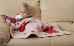 Baby reading book on sofa. Close up of cute baby girl relaxing under blanket on sofa looking at book Royalty Free Stock Image