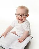 Baby reading with glasses. Portrait of an adorable baby sitting up wearing eyeglasses and looking at a book, isolated on white royalty free stock photos
