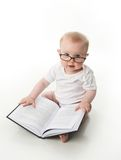 Baby reading with glasses. Portrait of an adorable baby sitting up wearing eyeglasses and looking at a book, isolated on white royalty free stock photo