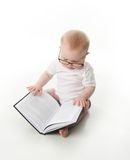 Baby reading with glasses. Portrait of an adorable baby sitting up wearing eyeglasses and looking at a book, isolated on white royalty free stock image