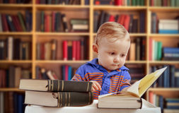 Baby reading in library - education concept. Little baby reading literature books in library interior with old books on the shelves - education concept royalty free stock photography