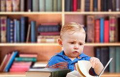 Baby reading in library royalty free stock photo