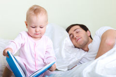 Baby reading to father Stock Images