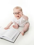 Baby reading wearing glasses. Portrait of an adorable baby sitting up wearing eyeglasses and looking at a book, isolated on white Royalty Free Stock Images