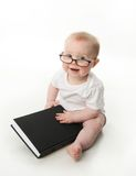 Baby reading wearing glasses. Portrait of an adorable baby sitting up wearing eyeglasses and looking at a book, isolated on white Stock Image
