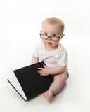 Baby reading wearing glasses. Portrait of an adorable baby sitting up wearing eyeglasses and looking at a book, isolated on white Royalty Free Stock Photo