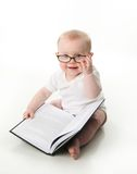 Baby reading wearing glasses. Portrait of an adorable baby sitting up wearing eyeglasses and looking at a book, isolated on white Royalty Free Stock Photos