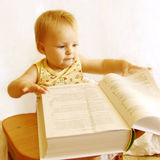 The baby reads the book Stock Image