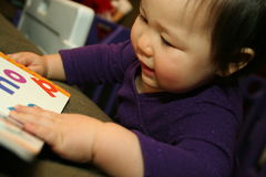 Baby reads her first book Stock Images