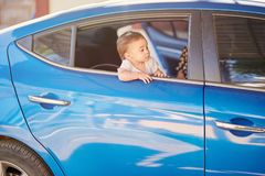 Baby ready to go on car. Looking from car window baby girl royalty free stock image