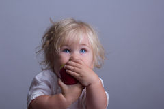 Baby a red apple. Baby with blond long hair holds a red apple Stock Photos