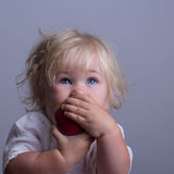 Baby a red apple. Baby with blond long hair holds a red apple Stock Images