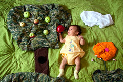 Baby and red apple in fairy tale. Little baby holding red apple laying on the bed with garden decoration on it: apple tree, orange flower, cloud and grass stock image